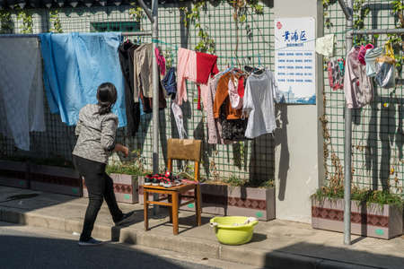 SHANGHAI, CHINA - 26 OCTOBER 2018: Chinese woman hanging out washing to dry on side of street in old city Imagens - 117884748
