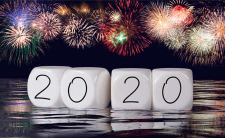 Multiple firework explosions against dark blue sky with calendar date and water reflections for 2020 New Years celebrations Stock Photo