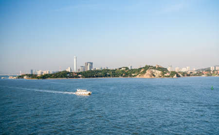 Ferry boat passes island of Gulangyu in foreground with background of Xiamen in China