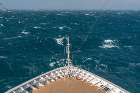 View from front at the rough seas and waves forward of bow of cruise ship Stock Photo