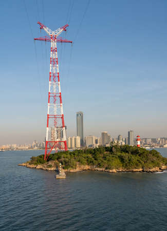 Tall electricity power tower on small island in harbor of Xiamen in China
