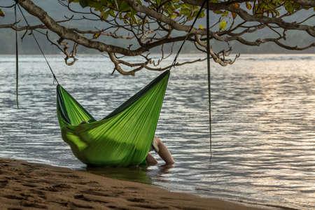 Rear view of romantic couple enjoying sunset in Kauai from hanging swinging hammock
