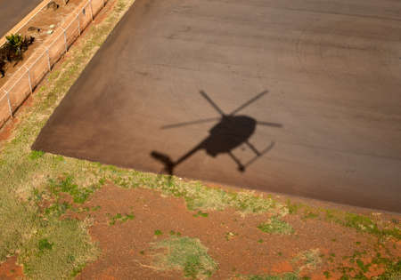 Shadow of small Hughes helicopter landing at Lihue in Kauai 写真素材