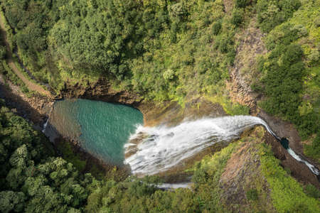 Aerial view of Manawaiopuna Falls and landscape of hawaiian island of Kauai from helicopter flight Imagens