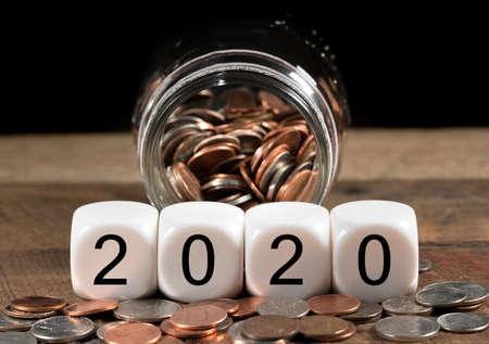 Cash in savings jar for good luck as dice for 2020 is spread on table for New Years celebrations Stockfoto - 116279712