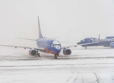 DENVER, COLORADO: JANUARY 24, 2019: Southwest plane on runway as second one passes behind in snow storm Stock Photo - 117885118