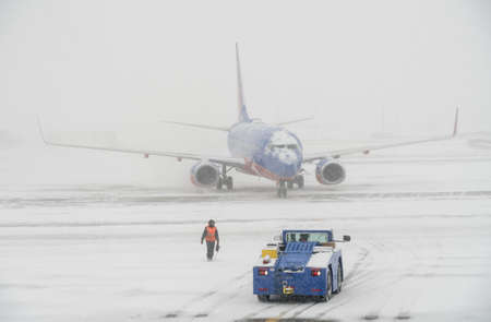 DENVER, COLORADO: JANUARY 24, 2019: Southwest plane being towed to the runway in snow storm Stock Photo - 117885119