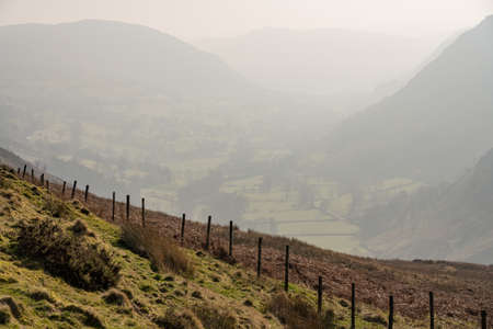 View besides road out of Llangynog in North Wales over the hills to Bala with misty valley behind Banco de Imagens