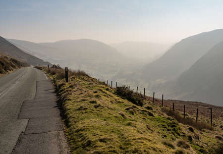 Narrow road out of Llangynog in North Wales over the hills to Bala with misty valley behind