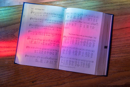 Colored light from stained glass window in methodist church falls across open hymnal for Easter hymn Stock Photo