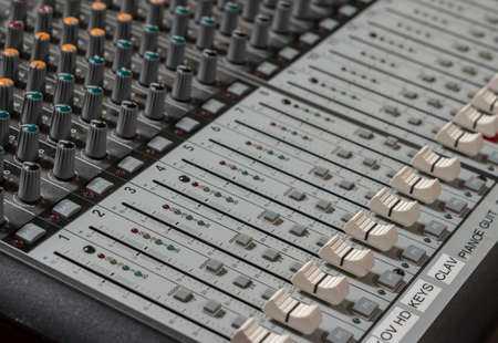 Sound mixing board with focus on the audio sliders for level from musical instruments