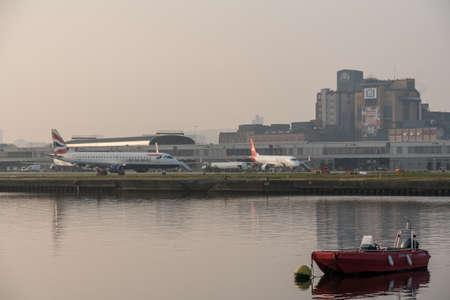 LONDON, UK - 17 APRIL 2019: Planes arrive at London City Airport on misty morning at sunrise