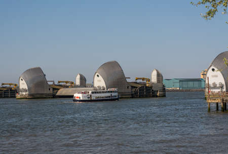 LONDON, UK - 21 APRIL 2019: Tourists on cruise boat by Thames Barrier in docklands of London near Greenwich
