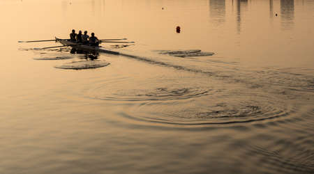 Sunrise lights up team of four rowers in canoe practicing in London Docklands