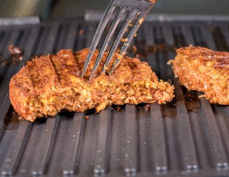 Primer plano de la carne como empanadas a base de plantas para hamburguesas de ternera vegetarianas a la parrilla en una plancha caliente