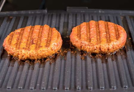 Close shot of the meat like plant-based patties for vegetarian beef burgers being grilled on hot griddle