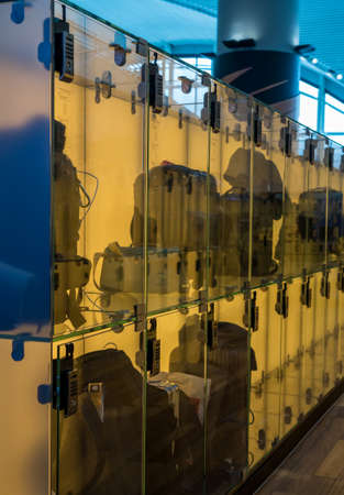 Modern luggage storage solution in airport with glass boxes for carry-on bags