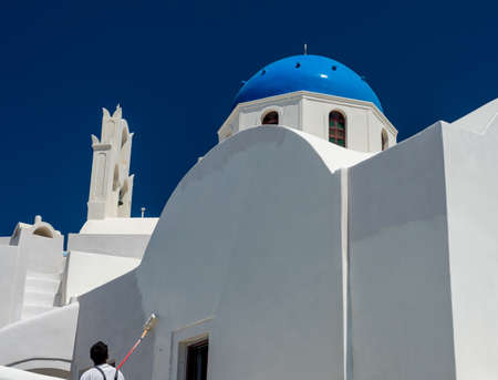 White paint being applied by roller to traditional house in Santorini