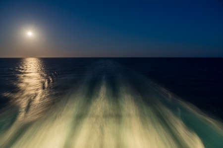 Moon rising over wake and waves of cruise ship at sea with concept of leaving or starting anew 写真素材