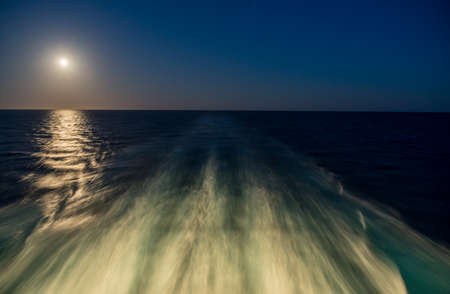 Moon rising over wake and waves of cruise ship at sea with concept of leaving or starting anew 写真素材 - 124640527
