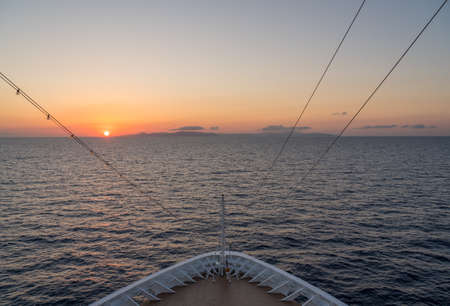 Small cruise liner sailing across the ocean as dawn starts to light the sky Stock Photo