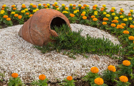Flowers and gravel surround ceramic urn in ornamental garden