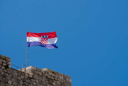 Flag of Croatia or the Tricolour flies on the stone walls of Dubrovnik