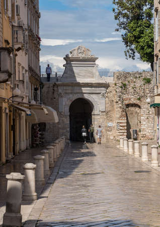 Zadar, Croatia - 23 May 2019: Tourists leave via the Sea Gate from the ancient old town of Zadar in Croatia