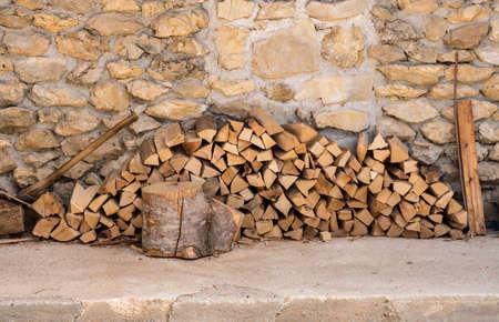 Gehacktes Holz und Axt gestapelt gegen die Steinmauer eines rustikalen Bauernhauses Standard-Bild
