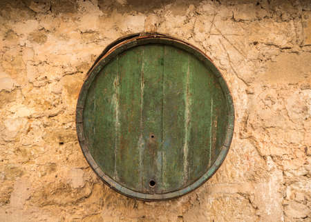 Old wooden barrel on stone farmhouse wall Banque d'images