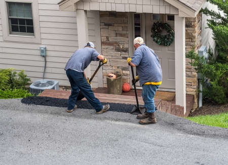 Two workers applying a layer of tarmac or extra blacktop onto asphalt street