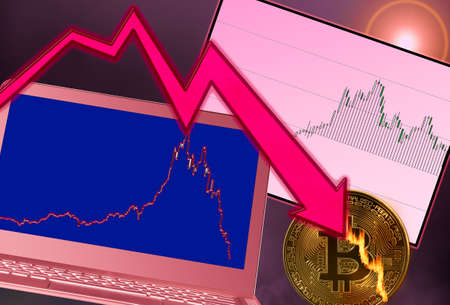 Concept of bitcoin or cyber currency on fire as price crash occurs. Laptop shows falling price graph