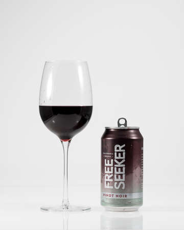 Morgantown, WV - 13 July 2019: Aluminum can of Free Seeker California Pinot Noir by red wine glass