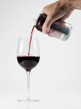 Senior man hand pouring a glass of red wine from a single serving can