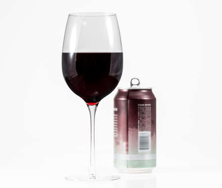 Aluminum can of California Pinot Noir behind a full glass of red wine showing move to single serving cans