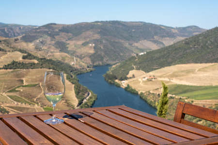 Glass of white wine for tasting above the hillsides of the Douro valley in Portugal