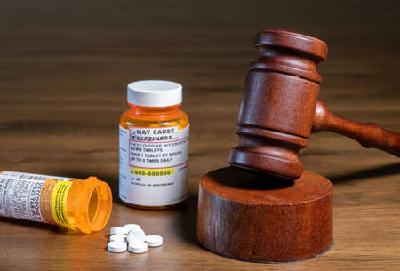 Oxycodone is the generic name for opoid pain killing tablets. Prescription bottle for pills and tablets with judges gavel for court decision