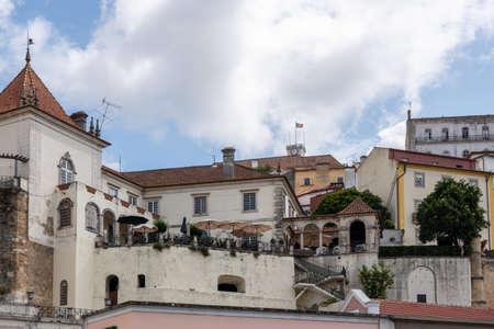Restaurant with balcony below University of Coimbra on hilltop above the city from Santa Clara bridge