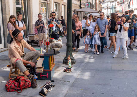 Porto, Portugal - 12 August 2019: Busker playing a card based music box or player piano in Oporto