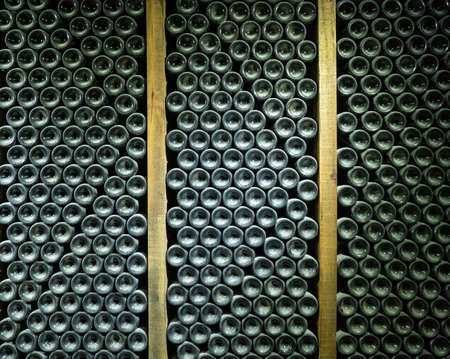 Stacks of wine bottles laying flat in wooden racks in old wine cellar or cave