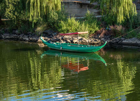 Fishing or rowing boat anchored in the calm waters on the bank of the River Douro in Portugal 免版税图像