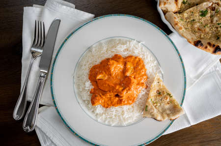 Chicken Tikka Masala with garlic Naan bread plated on white plate on napkin and taken from above