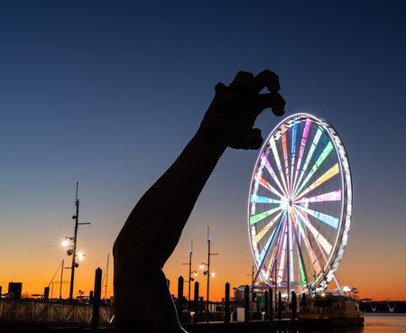 National Harbor, Maryland - 6 November 2019: Illuminated Capital Wheel with giant arm of The Awakening at National Harbor near Washington DC at sunset Publikacyjne