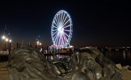 National Harbor, Maryland - 6 November 2019: Illuminated Capital Wheel with giant face of The Awakening at National Harbor Washington DC at sunset Publikacyjne