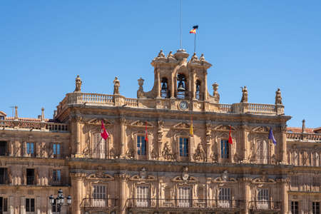 Flags fly over the windows of City Hall and clock tower in Plaza Mayor in Salamanca, Spain