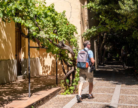 Senior adult photographer strolls through the Huerto de Calixto y Melibea gardens near the cathedrals in Salamanca Spain