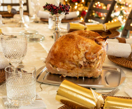 Turkey crown ready for carving on traditional British Christmas lunch table setting