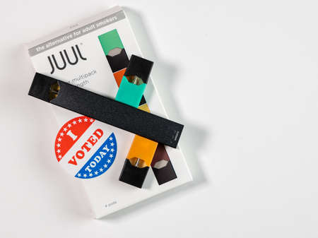 Morgantown, WV - 2 January 2020: Juul flavored nicotine vaping system with I Voted sticker to illustrate political issues with a ban