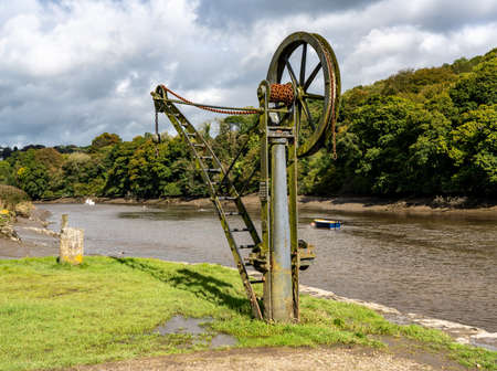 Rusty old metal winch or crane for cargo by the tidal River Tamar at Cotehele in Devon