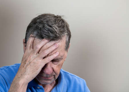 Head and shoulders portrait of a senior caucasian man with head in hands and looking depressed Reklamní fotografie